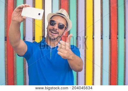 Hipster guy taking self portrait with smart phone against colorful wooden fence and showing thumbs up