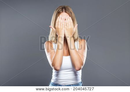 Beautiful Young Woman Covering Her Face Over Gray Background.