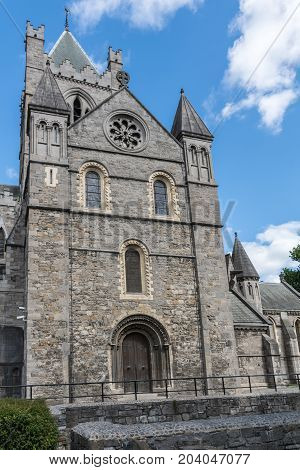 Dublin Ireland - August 7 2017: Gray stone bell tower of Christ Church Cathedral against blue sky with white clouds.
