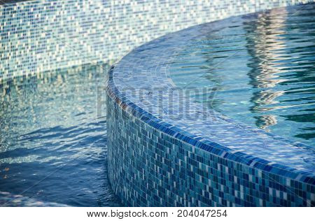 close-up edge of the swimming pool with blue mosaic tiles