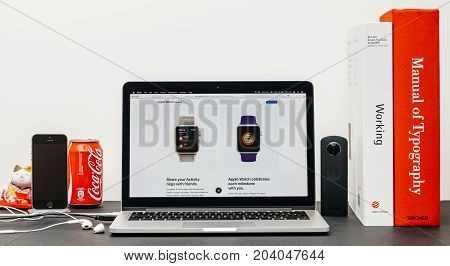 PARIS FRANCE - SEP 13 2017: Minimalist creative room table with Safari Browser open on MacBook Pro laptop at Apple Computers website with latest Apple Watch Series 3 with milestones and share app