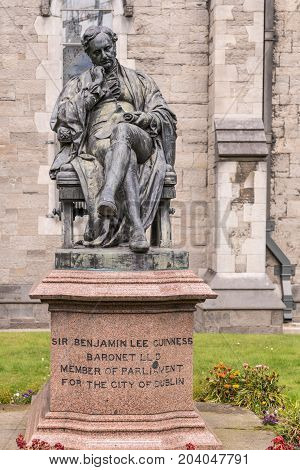 Dublin Ireland - August 7 2017: Closeup of Sir Benjamin Lee Guinness Statue in garden of Saint Patrick Cathedral. Wall of church in back.