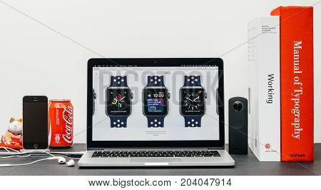 PARIS FRANCE - SEP 3 2017: Minimalist creative room table with Safari Browser on MacPook Pro laptop at Apple Computers website with latest Apple Watch Series 3 with selction of apple watc face band