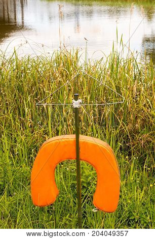 Lifesaver hanging from a pole by a lake