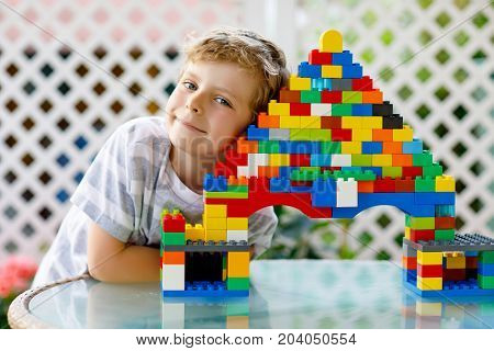 Little blond child playing with lots of colorful plastic blocks. Adorable school kid boy wearing colorful shirt and having fun with building big castle and creating a house.