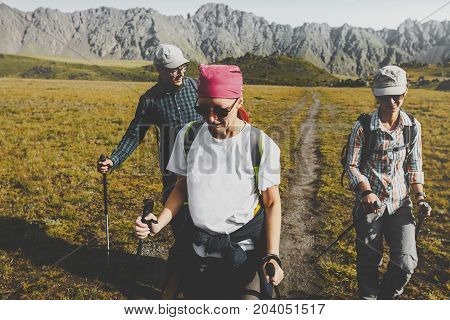Group Of Hikers Walking Along The Plain In Summer Mountains Journey Travel Trek Concept