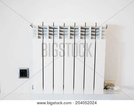 New white heating radiator on the white wall in the apartment