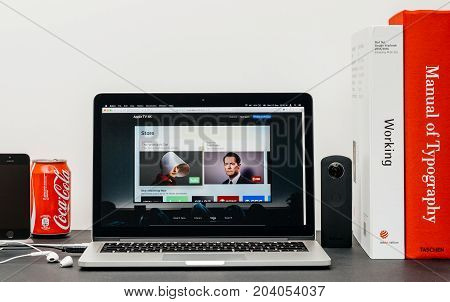 PARIS FRANCE - SEP 13 2017: Minimalist creative room table with Safari Browser open on MacBook Pro laptop showcasing Apple Computers website with latest Apple TV 4k with subscribe to itunes store