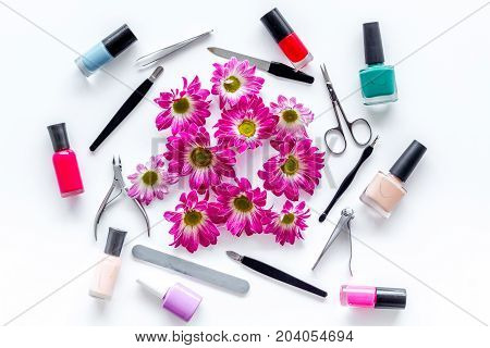 Choose nail polish for manicure. Bottles of colored polish on white background top view.