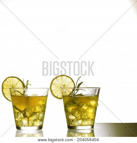 Two Yellow Cocktails With Lemon And Rosemary Standing On Glass In Studio, Isolated