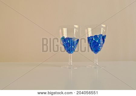 Two wineglasses with beautiful blue diamonds on the yellow background