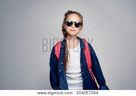 girl in sunglasses on gray background, smile.