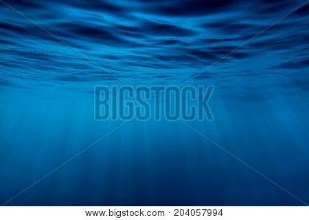 Water underwater and sun rays. Blue ocean in underwater
