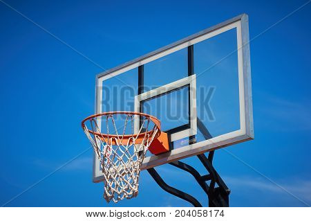 Basketball hoop and backboard with blue sky.