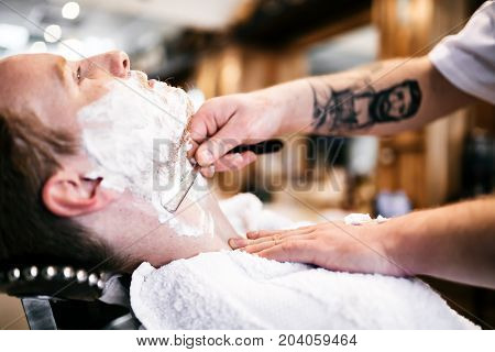 Retro shaving with foam in barber shop