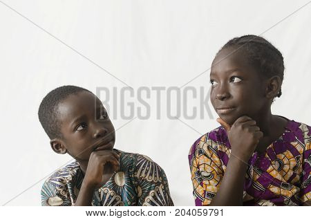 Two African children thinking with hands on their chins, isolated on white