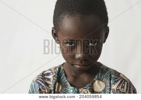 Young African boy showing his angry face, isolated on white