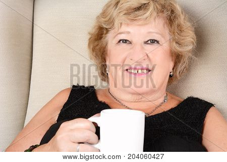 Portrait of an old woman drinking coffee and sitting on couch. Indoors.