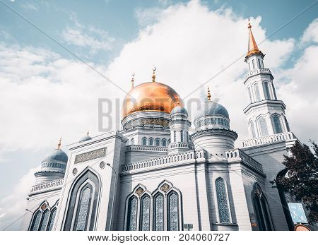 Wide angle view from bottom of The Grand Cathedral Mosque made of white stone with quotations from Quran on the golden dome sunny autumn day Moscow Russia