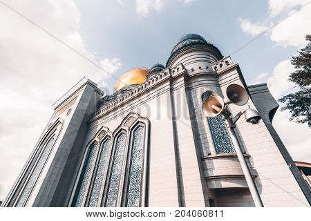 Wide-angle view from bottom side of The Grand Cathedral Mosque made of white stone: golden dome and spires loudspeaker for prayerful broadcasting and security camera in foreground Moscow Russia