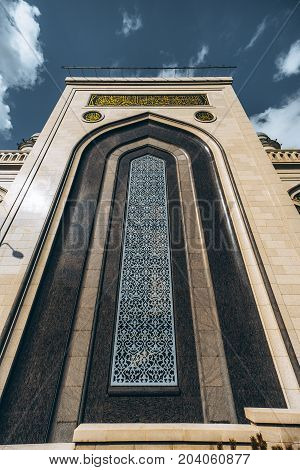 Vertical view from bottom of The Grand Cathedral Mosque beautiful ornamental facade made of stone; caption with quotation from Quran on the top Moscow Russia