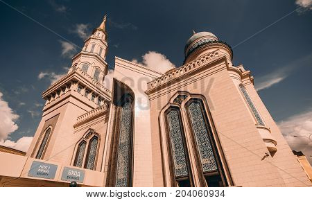 Side view from bottom of beautiful Grand Cathedral Mosque made of stone on sunset: teal fancy facade and golden spires quotation from Quran sunny autumn evening security entrance Moscow Russia