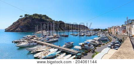 Panoramic view of the small harbor of Chiaiolella Marina with tourist boats moored at the dock. To the left the promontory of Punta della Palombara.