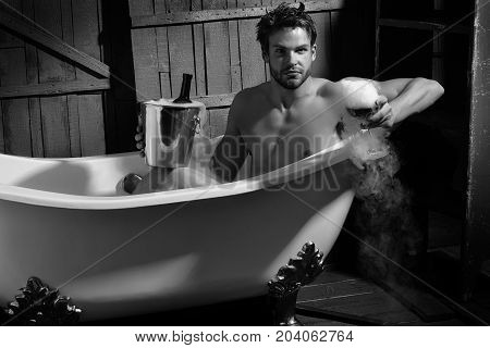 One handsome sensual sexy muscular young man with beautiful bare body sitting in white bath tub with foam holding glass with luquid smoke and bottle in pile on wooden wall backdrop horizontal picture