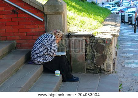 Lviv - circa August 2013 / Ukraine: grandmother asks for alms and sleeps while reading a book at the same time at church stairs. circa August 2013 in Lviv, Ukraine.