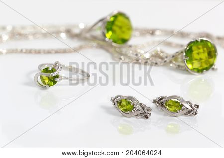 Close-up beauty silver earrings and small ring with peridot on background pendant chain and big ring on white acrylic desk.