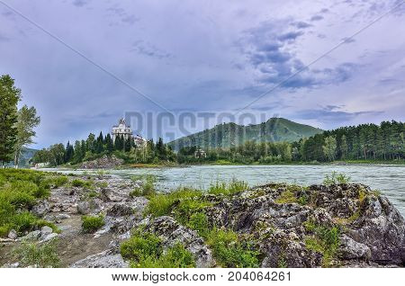 Rocky island on the mountain river Katun (Russia) - summer landscape Picturesque summer landscape of rocky island on the mountain river Katun (Altai Republic Russia) and part of hotel building