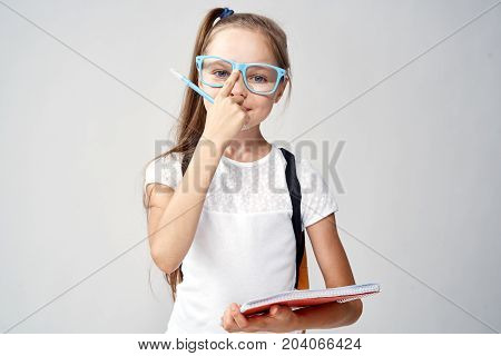 the girl adjusts glasses with a pencil in her hand.