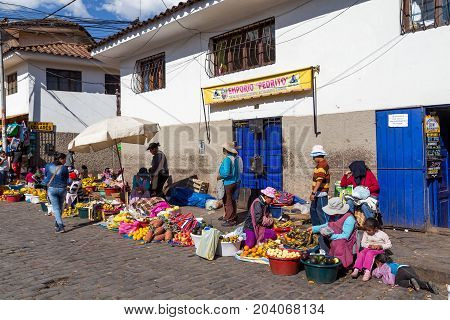 Cusco, Peru - August 08, 2015: People selling and buying fruits at a market in the steets
