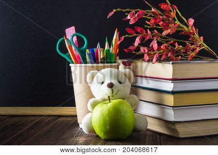 Concept Of Teacher's Day. Objects On A Chalkboard Background. Books, A Green Apple, A Bear, Pencils