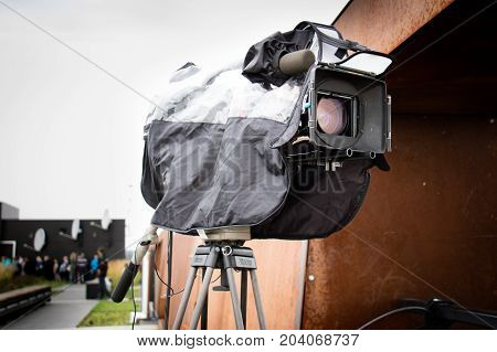 Movie camera mounted on a tripod in a rain cover. In the background City of Gdansk.
