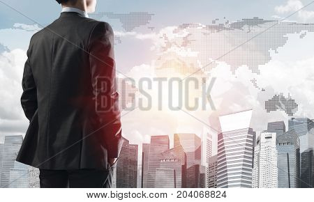 Young elegant businessman with hands in pockets looking away