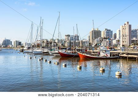 Maldonado September 5 2017: Classic Red Fishing Boats moored in front of the yachts of the rich people in Punta del Este harbor Uruguay