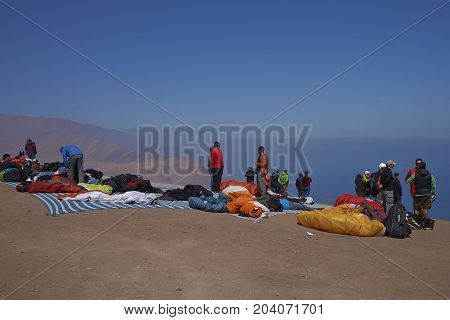 Iquique, Tarapaca Region, Chile - August 20, 2017: Group of people and paraglider waiting for suitable conditions to take off over the coastal city of Iquique on the northern coast of Chile.