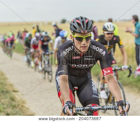 QuievyFrance - July 07 2015: Environmental portrait of the German cyclist Andreas Schillinger of Bora-Argon 18 Team inside the peloton riding on a cobblestoned road during the stage 4 of Le Tour de France 2015 in Quievy France on 07 July2015.