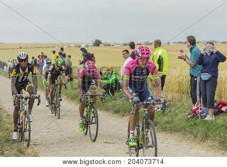 QuievyFrance - July 07 2015: Group of cyclists riding on a cobblestoned road during the stage 4 of Le Tour de France 2015 in Quievy France on 07 July2015.