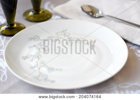 Empty plate on an arranged table, white plate with pattern