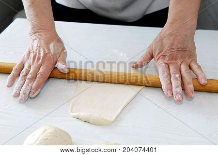 Woman unrolls dough with rolling pin on a table