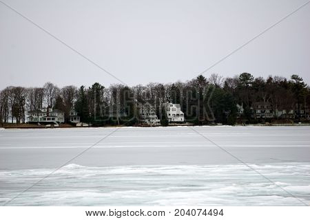 A view of Harbor Point homes, across ice-covered Little Traverse Bay, as seen from the beach in Wequetonsing, Michigan, during March.
