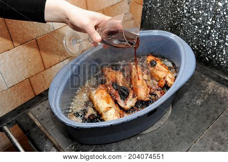 Pouring wine on chicken specialty with plums