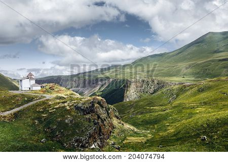 Abandoned House On Top Of Hill In Background Of Picturesque Mountain Landscape