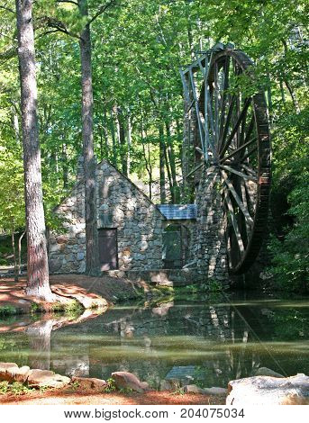 a stone gristmill with a large wheel reflected in a pond