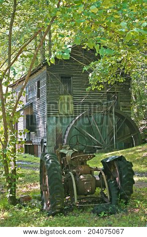 an old gristmill behind a rusty tractor