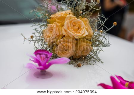 Close-up Of Wedding Bouquet Made Of Yellow Roses On White Limousine Hood