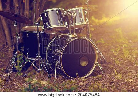 Set Of Black Battery Drum Set Under The Tree On The Grass. Vintage Tone