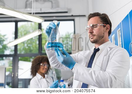 Serious Scientist Looking At Flask With Blue Liquid In Laboratory Over Group Of Scientific Researchers Making Experiments In Modern Lab